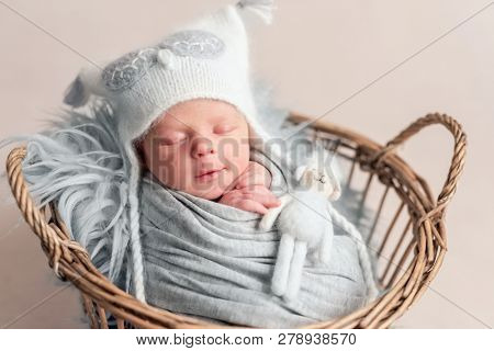 Top view of baby in white knitted hat sleeping in basket covered in blanket