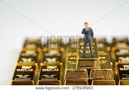 Success Wealth Management Concept, Miniature Figure Businessman Standing On Stack Of Shiny Gold Bar