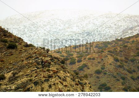 Arid Hills With Chaparral Shrubs Including Snow Capped Mountains In The Higher Elevations Beyond Tak