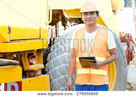Portrait Of Smilng Vietnamese Construction Site Worker Standing With Tablet Computer At His Big Truc