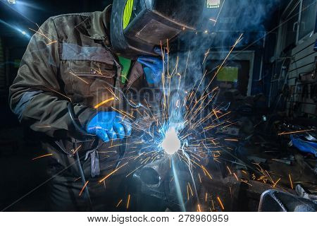Man Welder In Welding Mask, Building Uniform And Blue Protective Gloves Welds Metal Car Muffler With