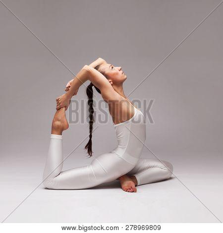 Young Beautiful Woman Yoga Posing On Isolated Light Grey Gradient Studio Background