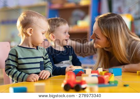 Nursery Children Building Blocks With A Teacher In Preschool Playroom