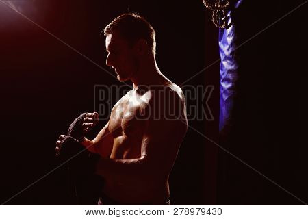 Kickboxing Concept. Muscular Man Prepare For Kickboxing. Fit Sportsman Wrapping Up In Kickboxing Gym