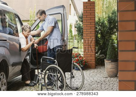 Son Is Helping His Elder Mother To Get Out Of The Car