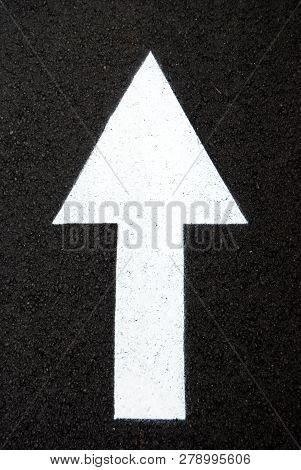 Vertical White Arrow Drawn On Black Asphalt