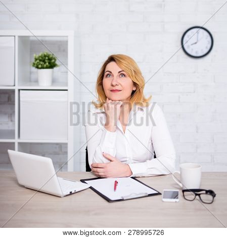 Cheerful Mature Business Woman Sitting In Modern Office And Dreaming About Something