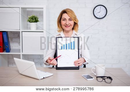 Business Plan Concept - Cheerful Mature Business Woman In Office Showing Clipboard With Charts And G