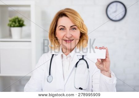 Portrait Of Cheerful Mature Woman Doctor Showing Her Visiting Card