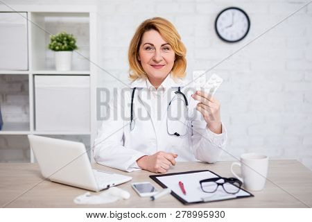 Mature Female Doctor Showing Pills In Modern Office Or Pharmacy Store
