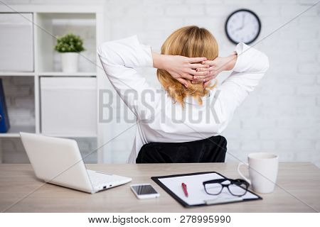 Back View Of Mature Business Woman Relaxing With Her Hands Behind Her Head And Dreaming About Vacati