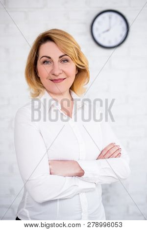 Mature Business Woman Posing Over White Brick Wall With Office Clock