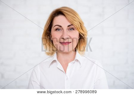 Close Up Portrait Of Mature Woman Over White Brick Wall