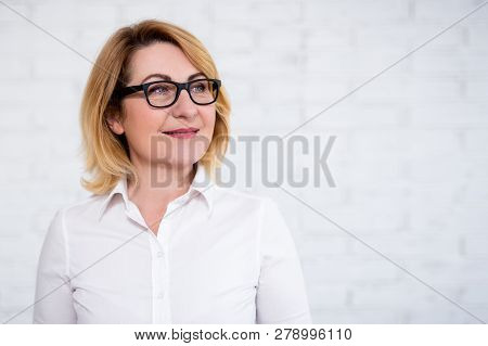 Business Idea Concept - Portrait Of Thoughtful Cheerful Mature Business Woman In Eyeglasses Posing O