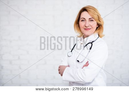 Mature Female Doctor Or Nurse Posing Over White Brick Wall With Copy Space
