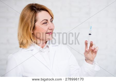 Health Care, Vaccination And Cosmetology Concept - Portrait Of Mature Female Doctor Holding Syringe