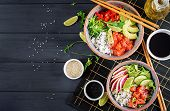 Hawaiian salmon fish poke bowl with rice, avocado, paprika, cucumber, radish, sesame seeds and lime. Buddha bowl. Diet food. Top view poster
