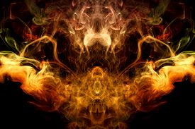 Thick Colorful Smoke Of Yellow And Orange  In The Form Of A Skull, Monster, Dragon On A Black Isolat