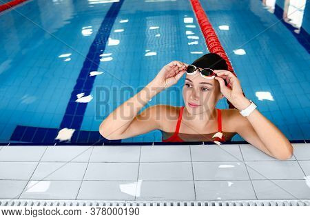Portrait Of A Female Swimmer In Swimming Goggles In The Pool After Training. Swimming Goggles Help T