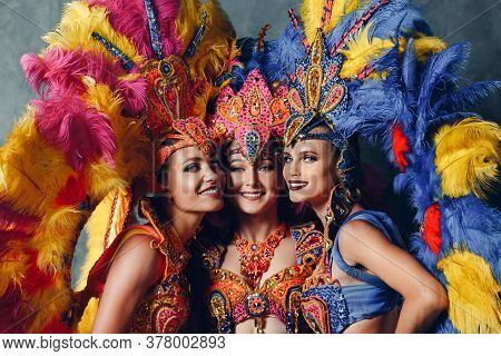 Three Women Smiling Portrait In Brazilian Samba Carnival Costume With Colorful Feathers Plumage