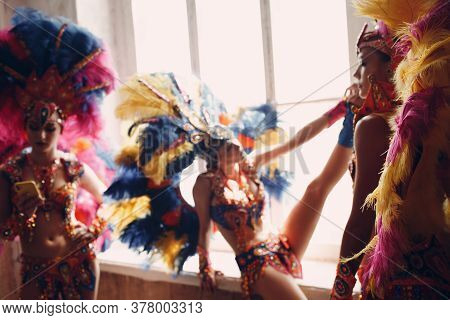 Woman In Brazilian Samba Carnival Costume With Colorful Feathers Plumage Relax In Old Entrance With