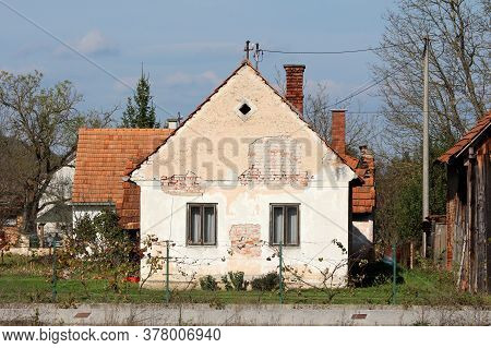 Abandoned Small Old Red Bricks Suburban Family House With Cracked Facade And Two Dilapidated Wooden