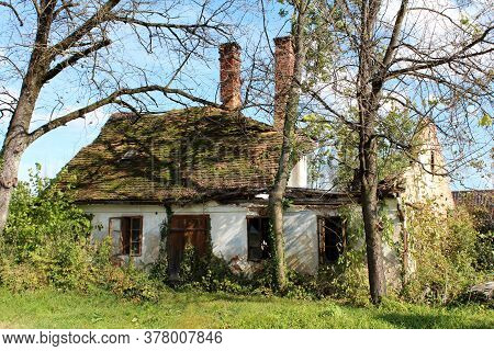 Ruins Of Small Old Abandoned Suburban Family House With Destroyed Roof Partially Covered With Moss A