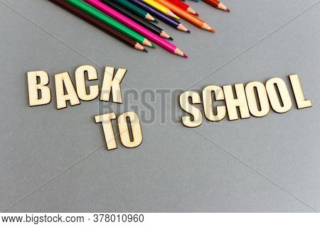Phrase Back To School Made Of Wooden Letters On Gray Background. Set Of Multi-colored Pencils For Sc