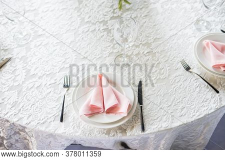 Close Up Festive Table Setting With Empty Wineglasses. Selebration Banquet With White Plates, Pink N