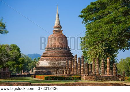 Buddhist Stupa On The Ruins Of Ancient Temple In The Historical Park Of Sukhothai On A Sunny Day. Th