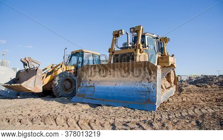 Dozer And Loader Working At Construction Site. Bulldozer For Land Clearing, Grading, Pool Excavation