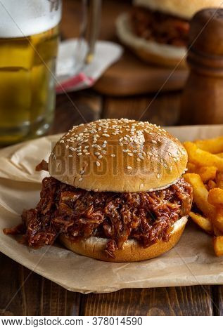 Barbecue Pulled Pork Sandwich On A Sesame Seed Bun With French Fries