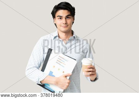 Portrait Of Overworked Young Businessman With Documents Having Coffee To Stay Awake