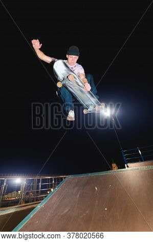 A Young Skater At Night In A Skatepark Does The Trick On The Railing. X-ray Culture Nightlife Concep