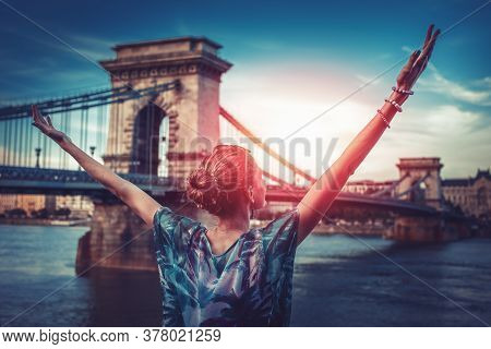 Beautiful Grateful And Thankful Young Urban Woman Arms Raised In Sunrise At City. Travel Destination