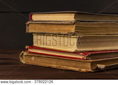 Vintage, Antiquarian Books Pile On Wooden Surface In Warm Light. Selective Focus. Old Books Stacked