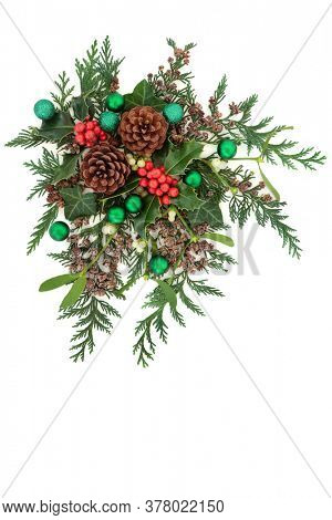 Christmas composition with green baubles & winter greenery with holly, mistletoe, ivy, pine cones & cedar cypress fir on white background. Xmas & New Year decorative display. Flat lay.