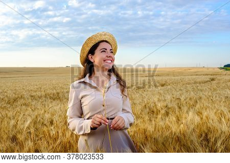 Young Long-haired Woman In A Straw Hat Holds Stalk Of Wheat And Smiling In Field