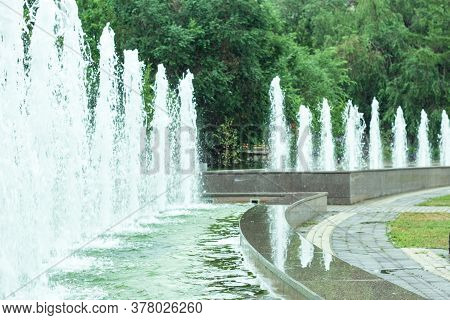 Public Jet Fountains In Urban Park Area, Close Up Of Water Jets And Refreshing Splashes Over Emerald