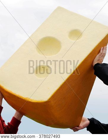 Two People Holding Up A Big Piece Of Emmental Or Swiss Cheese With Holes