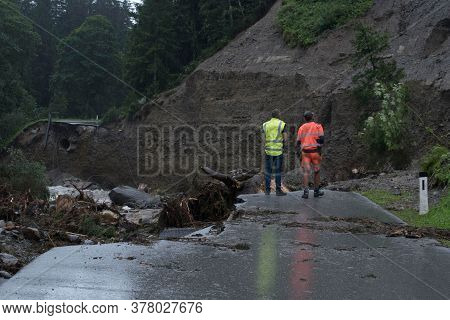 Two Geologists In Safety Vests Standing In Front Of A Collapsed Road