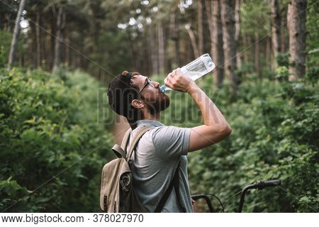 A Young Male Cyclist Drinks Water From A Plastic Bottle At A Halt In The Forest. Tourism, Active Lif