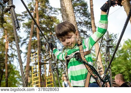 Boy Climbs In A High Wire Park Above The Ground. Ziplining. Boy On The Zip Line. Kid Passes The Rope