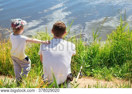 Father And His Son Sit On The Shore Of The Lake With Rod And Catch Fish. Concept Of Outdoor Recreati