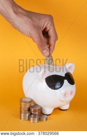 Cute Piggy Bank And Coins. Yellow Background Money Saving Concept. Closeup Hand Puts Coin Into Piggy