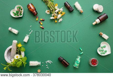 Alternative Herbal Medicine. Homeopathic Globules, Fresh Wild Flowers And Herbs Flat Lay On Green Ba
