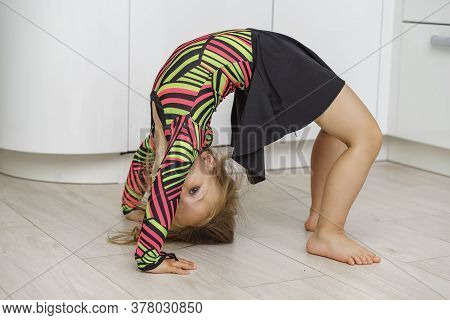 Beautiful Girl 4 Years Old In A Gymnastic Leotard Is Engaged In Gymnastics At Home In The Kitchen. P