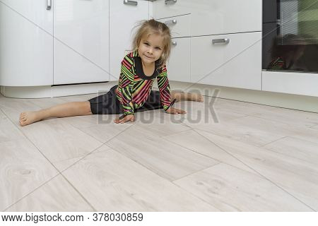 Beautiful Girl 4 Years Old In A Gymnastic Leotard Is Engaged In Gymnastics At Home In The Kitchen. S