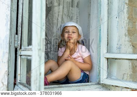 A Little Girl In Shorts Sits At The Window Of An Old Village House Thinking And Smiling. Summer Vaca
