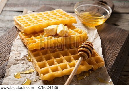 Plate With Delicious Waffle Honey And A Slice Of Butter. On A Wooden Background. Close-up